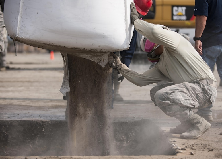 U.S. Air Force Staff Sgt. Ronald Jay Tabago, 8th Civil Engineer Squadron operations manager, cuts open a bag of rapid-set concrete during rapid airfield damage repair training at Kunsan Air Base, Republic of Korea, Oct. 25, 2017. Members from the Air Force Civil Engineer Center, Tyndall Air Force Base, Fla., instructed Airmen assigned to the 8th CES on the new RADR process. (U.S. Air Force photo by Staff Sgt. Victoria H. Taylor)