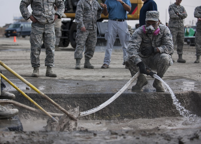 U.S. Air Force Senior Airman Sean Persaud, 8th Civil Engineer Squadron Water and Fuel Systems Maintenance journeyman, fills a damaged area with water while Airmen simultaneously mix in rapid-set concrete during rapid airfield damage repair training at Kunsan Air Base, Republic of Korea, Oct. 25, 2017. Members from the Air Force Civil Engineer Center, Tyndall Air Force Base, Fla., instructed Airmen assigned to the 8th CES on the new RADR process. (U.S. Air Force photo by Staff Sgt. Victoria H. Taylor)