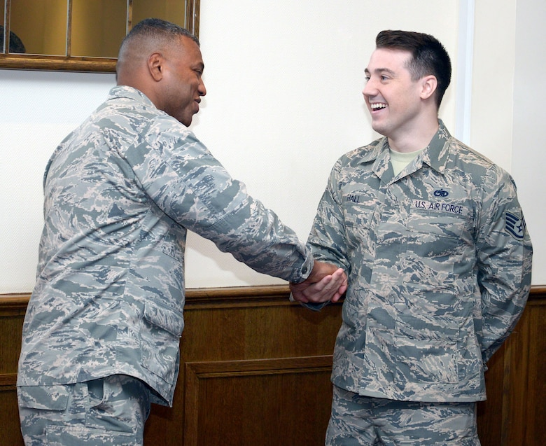 U.S. Air Force Lt. Gen. Richard M. Clark, 3rd Air Force commander, presents a coin to Staff Sgt. Alan Hall, 100th Maintenance Squadron sheet metal craftsman, for superior on-the-job performance Nov. 6, 2017, on RAF Mildenhall, England. Clark presented several Airmen with coins during his visit to recognize their hard work. (U.S. Air Force photo by Airman 1st Class Benjamin Cooper)