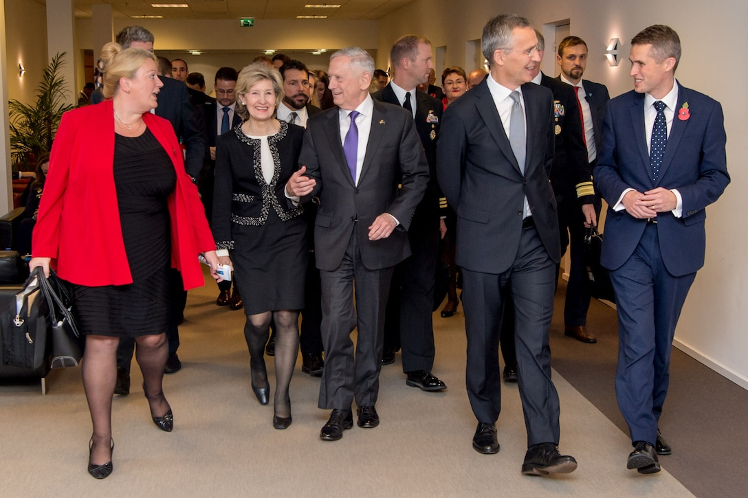 Defense leaders walk down a hallway at NATO headquarters.