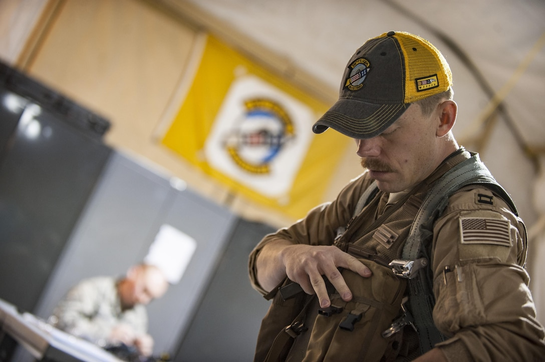 An aircrew member assigned to the 336th Expeditionary Fighter Squadron prepares his weapons and survival equipment for a sortie in support of Operation Inherent Resolve objectives November 7, 2017 in Southwest Asia.  In addition to the equipment required to safely operate high-performance combat aircraft, aircrew members also carry items designed to help them survive and get to safety in the event of a mishap. (U.S. Air Force photo by Senior Airman Joshua Kleinholz)