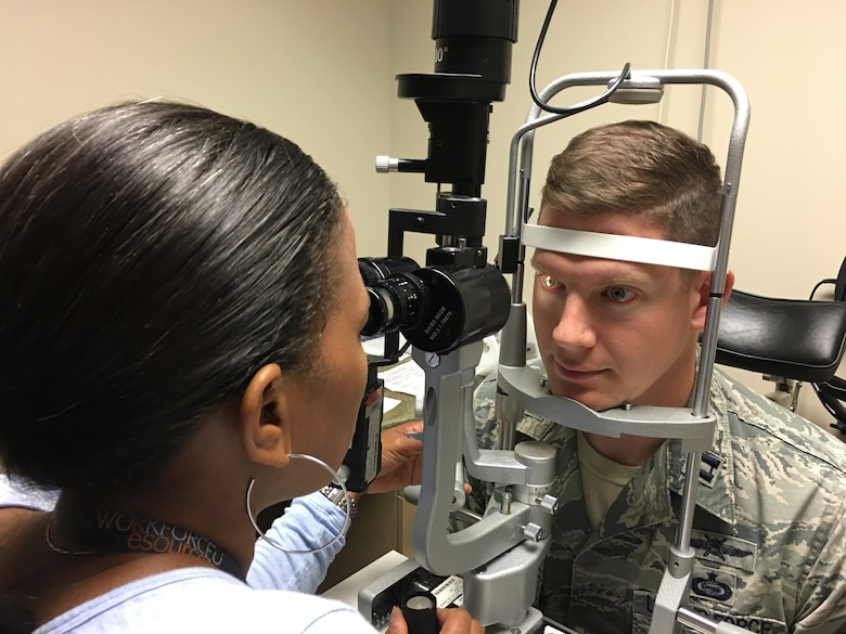 Dr. Nikki Meadows, 11th Medical Group Refractive Optometrist checks the health and stability of Capt Mark Kreul, patient, at the Warfighter Eye Center after completing refractive surgery.