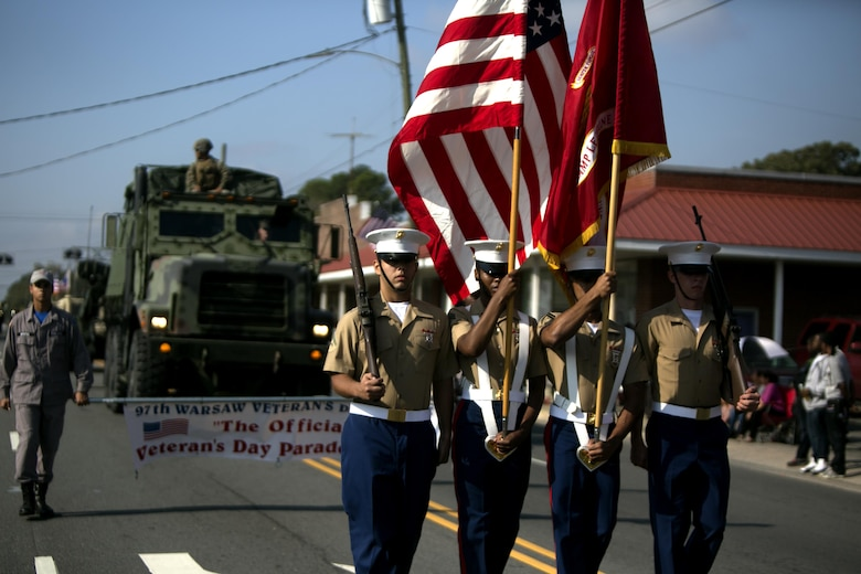Marines with Headquarters and Support Battalion, Marine Corps Installations - East march as the color guard during the Warsaw Veterans Day Parade