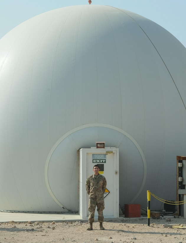 CAMP BUEHRING, Kuwait – Sgt. Richard Bosquez, F Company, 2-149th General Support Aviation Battalion's acting facility chief at Udairi Landing Zone, poses for a picture in front of the Radome, which houses the Air Traffic Navigation, Integration, Coordination System at Camp Buehring, Kuwait, Oct. 19, 2017. F Co. Soldiers provide air traffic services and airfield management at multiple locations in both Kuwait and Iraq. (U.S. Army photo by Capt. Stephen James)