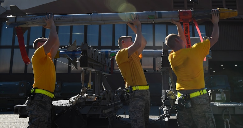The 27th Aircraft Maintenance Unit load crew lift an AIM-9X missile during the 3rd Quarter Weapons Load Competition at Joint Base Langley-Eustis, Va., Nov. 3, 2017.