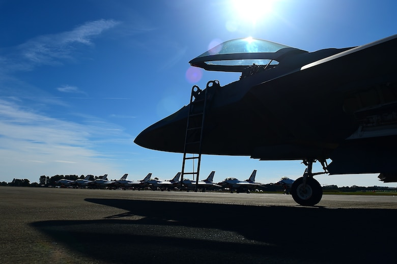 F-22 Raptor sits on runway across from Thunderbirds