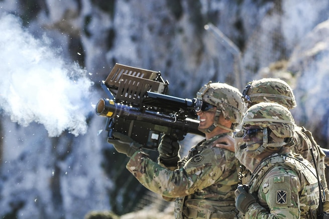 Three soldiers fire a shoulder mounted missile system.