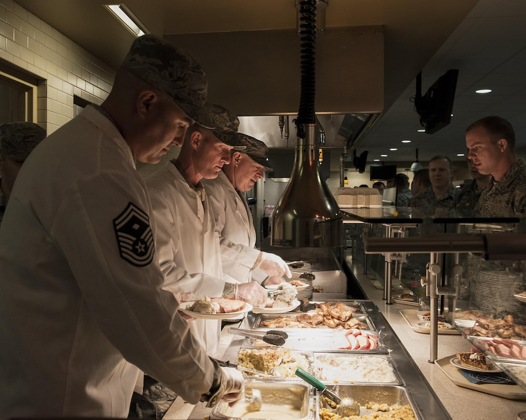 Senior Master Sgt. Jeffery Wiyrick, first sergeant for the 141st Air Refueling Wing, serves a holiday lunch alongside Command Chief Master Sgt. David Bishop and Col. Mark Fischer, 141st vice wing commander, Nov. 4, 2017 in the Warrior Dining Facility on Fairchild Air Force Base, Wash. More than 600 Airmen and Soldiers were served a holiday lunch over the November Unit Training Assembly weekend. (U.S. Air National Guard photo by Staff Sgt. Rose M. Lust/Released)