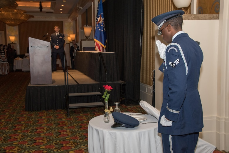 An Airman from the Barksdale Air Force Base Honor Guard salutes the POW/MIA Table during the 307th Bomb Wing Senior Noncommissioned Officer Induction and Chief Recognition Ceremony in Shreveport, La. Nov. 4, 2017.