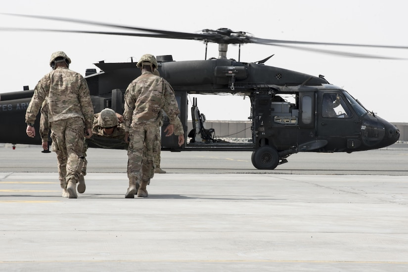 Two Soldiers carry another on a litter towards a helicopter.