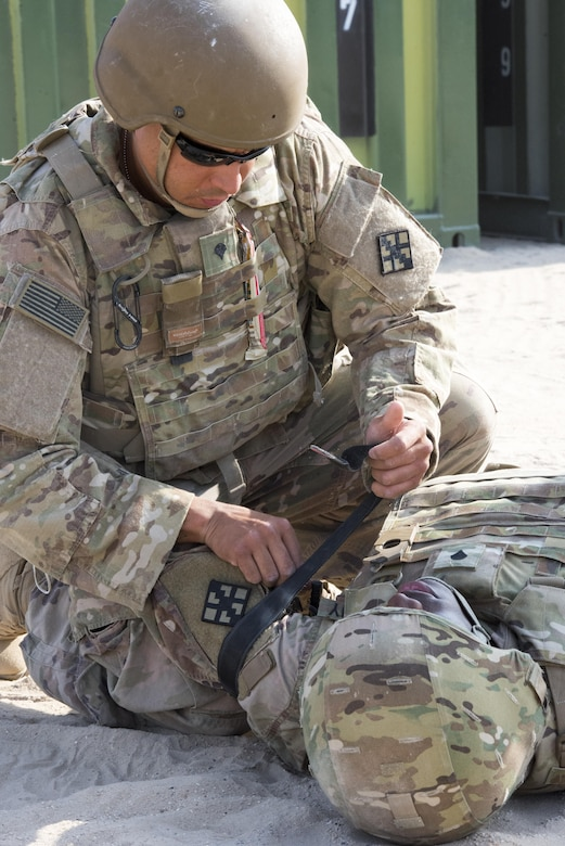 Soldier applies a tourniquet to another Soldier.