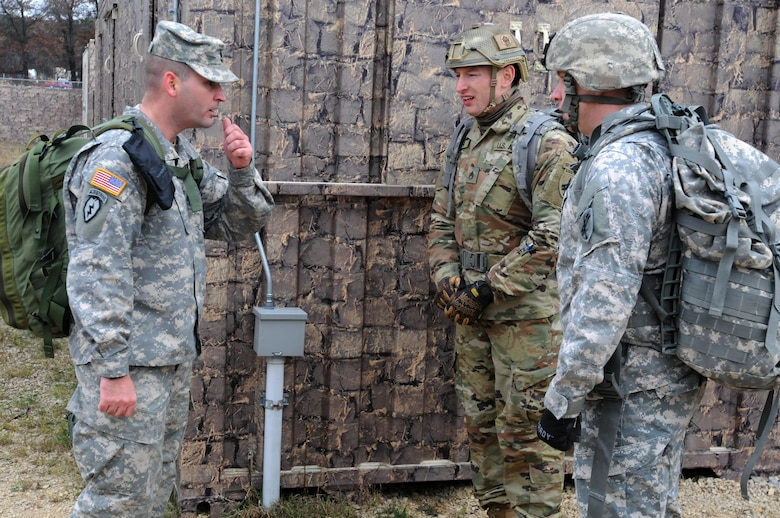 Sergeant 1st Class Nuhi Zhuta, left, from the 304th Civil Affairs Brigade, asks medical related questions to Staff Sgt. Loren Keeler, center, and Sgt. NAME Hardy, two best warrior competitors through some callisthenic exercises during the medical evaluation portion of the competition at Fort McCoy, Wisconsin, November 1, 2017.