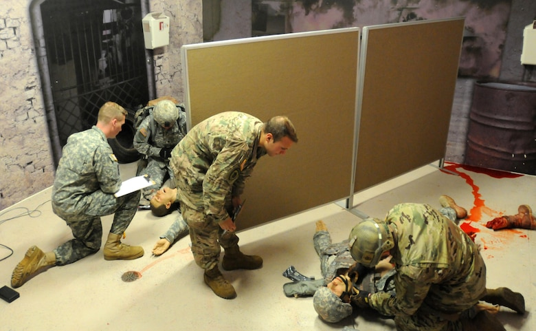 Best Warrior competitors Staff Sgt. Loren Keeler, right, and Sgt. Thomas Hardy, assess and treats a simulated casualty under the watchful eyes of judges Sgt. Brian Duckworth, right, and Staff Sgt. Dave Schulz, during the competition conducted by 353rd Civil Affairs Command at Fort McCoy, Wisconsin, November 1, 2017. Keeler went on to win the title of 353rd CACOM 2017 Non-Commissioned Officer of the Year. (U.S. Army Reserve photo by Zach Mott, 88th Regional Support Command Public Affairs Office)