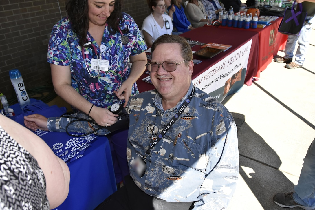A healthcare professional takes the blood pressure of an AEDC team member, Michael Glennon, during the Arnold Air Force Base Community Health Fair Sept. 29 in front of the Arnold Air Force Base Exchange and Commissary. More than 10 healthcare exhibitors from several community partners to include the Coffee County Health Department, Veteran's Affairs, Red Cross and Tennova Hospital, participated in the health fair. (U.S. Air Force photo/Rick Goodfriend) (This image was manipulated by obscuring badges for security purposes.)