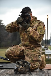Specialist Pedro Benavides, from 407th Civil Affairs Battalion, dons his gas mask during the 353rd Civil Affairs Command Best Warrior Competition at Fort McCoy, Wisconsin, November 2, 2017. (U.S. Army Reserve photo by Catherine Lowrey, 88th Regional Support Command Public Affairs Office)