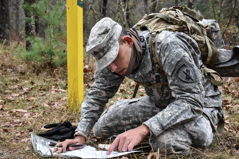 Sergeant Dyami Kellyclark, 443rd Civil Affairs Battalion, plots grid coordinates during the Land Navigation Course at the 353rd Civil Affairs Command Best Warrior Competition at Fort McCoy, Wisconsin, November 3, 2017.