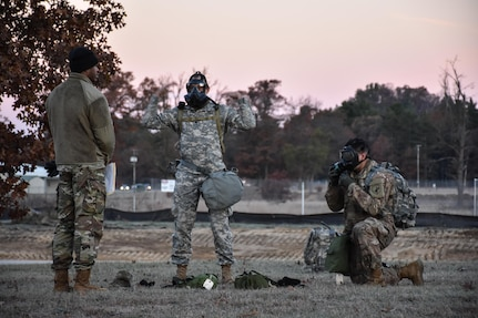 Staff Sgt. Loren Keeler, 407th Civil Affairs Battalion, and Spc. Pedro Benavides, from 407th Civil Affairs Battalion, don their gas masks during the Army Warrior Task lanes while participating in the 353rd Civil Affairs Command Best Warrior Competition at Fort McCoy, Wisconsin, November 3, 2017. (U.S. Army Reserve photo by Catherine Lowrey, 88th Regional Support Command Public Affairs Office)