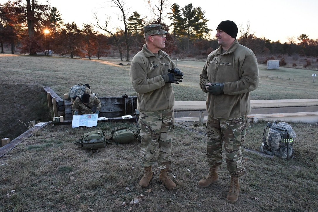 U.S. Army Civil Affairs & Psychological Operations Command (Airborne) Command Sgt. Maj. Pete Running, left, talks with 353rd Civil Affairs Command Sgt. Maj. Stephen Coville, right, during the Army Warrior Task lanes at the 353rd Civil Affairs Command Best Warrior Competition at Fort McCoy, Wisconsin, November 3, 2017. (U.S. Army Reserve photo by Catherine Lowrey, 88th Regional Support Command Public Affairs Office)