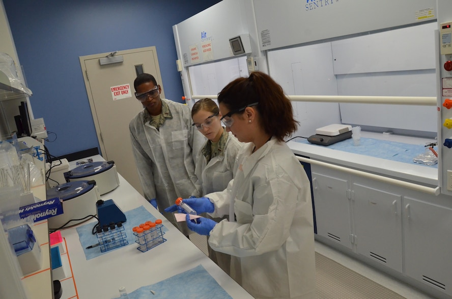 Melissa Dawkins (right), a chemist at the Ciambrone Radiochemistry Laboratory, Patrick AFB, Fla., explains to newly-assigned chemists 2nd Lts. Kaleb Mitchell (left) and Jessica Lewer (center) how samples that undergo radiochemical separations are inspected.  Scientists from CRL, which is headquartered at the Air Force Technical Applications Center, use analytical chemistry methods to determine if trace levels of radioactive debris are present in environmental samples as part of AFTAC's nuclear treaty monitoring mission.  (U.S. Air Force photo by Susan A. Romano)
