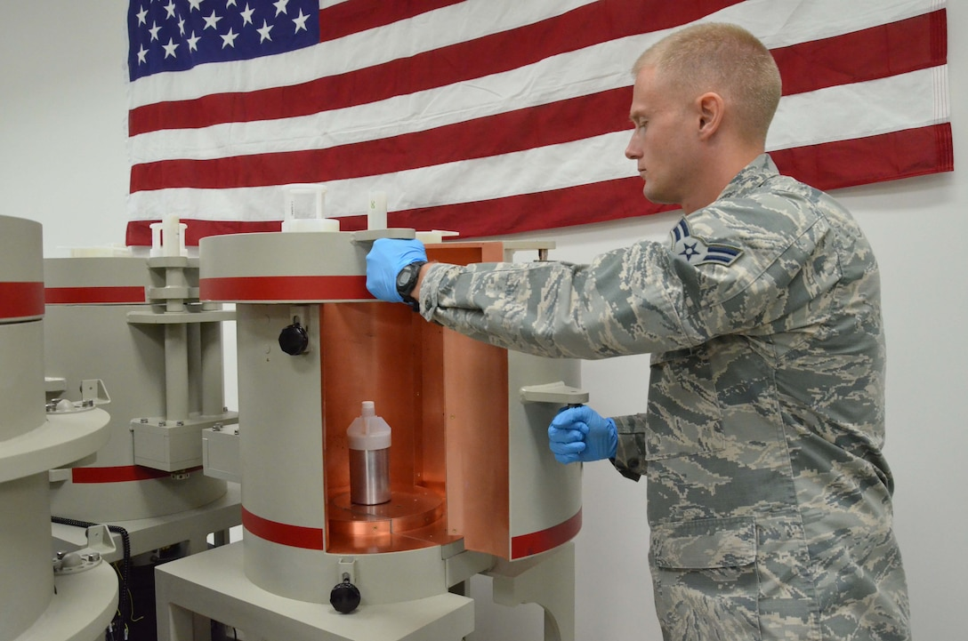 Airman 1st Class  Mitchell Kirkpatrick, a measurements technician at the Ciambrone Radiochemistry Laboratory, Patrick AFB, Fla., carefully places a sample onto a gamma ray detector to check for radioactive debris from an environmental sample.  The detector is made up of a 4-inch thick outer shell with a copper lining, which shields the sample and limits natural radioactivity and x-rays emitted from outside sources to prevent interference with low-level analysis.  (U.S. Air Force photo by Susan A. Romano)
