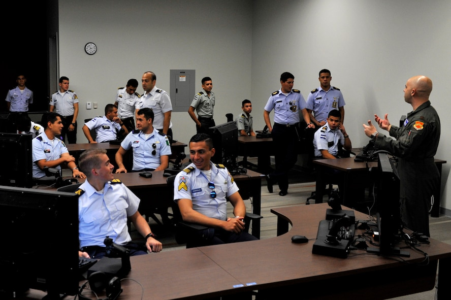 Maj. Adam Vogel, 56th Operations Group F-35 instructor pilot, instructs a class on how to fly an F-35A Lightning II on a desktop simulator at Luke Air Force Base, Ariz. Nov. 6, 2017. The Latin American Cadet's Initiatives program toured through the U.S. for approximately three and a half weeks. (U.S. Air Force photo/Airman 1st Class Pedro Mota)