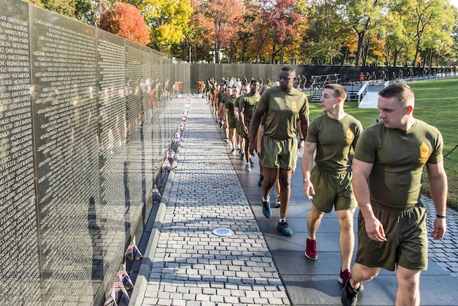 Marines in running wear walk in a line along the Vietnam Veterans Memorial, reading the names on the wall.