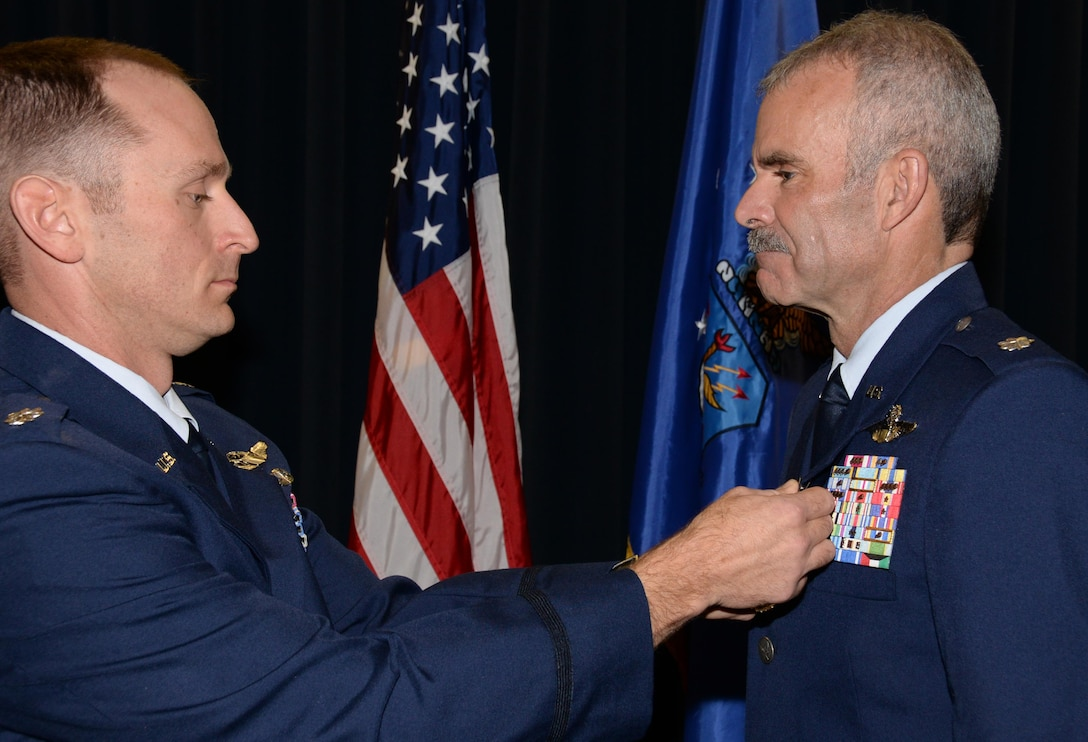 Lt. Col. Richard Pantusa, left, the 302nd Operations Group commander, pins the Meritorious Service Medal onto Lt. Col.  Luke Thompson's service dress uniform, during Thompson's retirement ceremony at Peterson Air Force Base, Colo. Nov. 4, 2017.
