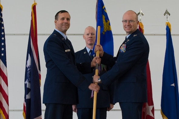 U.S. Air Force Brig. Stephen Rader passes the 153rd Airlift Wing guidon to incoming commander Col. Justin Walrath.