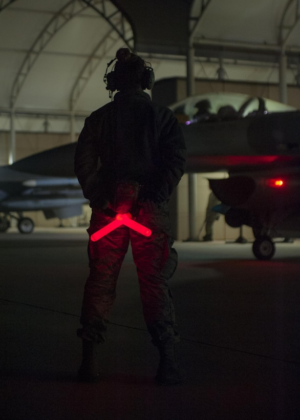 An Airman with the Wisconsin Air National Guard's115th Fighter Wing awaits the signal from her pilot to marshal their F-16 Fighting Falcon onto the taxiway at Kunsan Air Base, Republic of Korea, Nov. 4, 2017. The aircraft departed early in the morning for their journey back to Wisconsin after a three month deployment in support of a U.S. Pacific Command Theater Security Package. (U.S. Air Force photo by Capt. Christopher Mesnard)