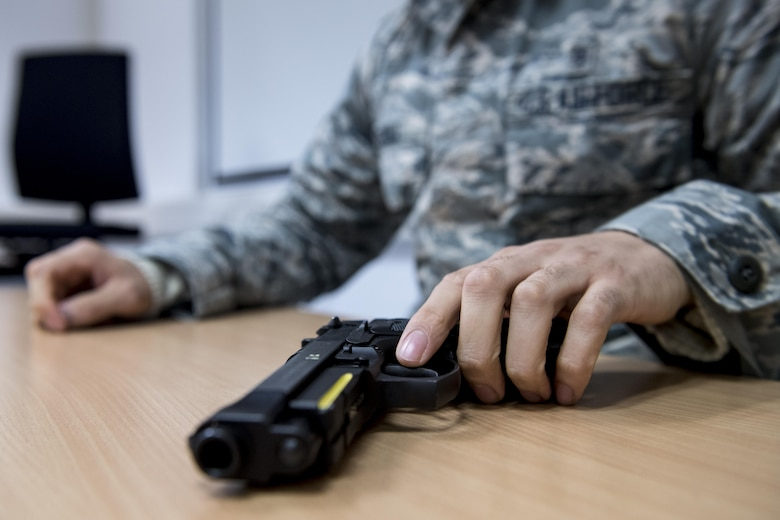 U.S. Air Force Airman 1st Class Alec Serna, 86th Security Forces Squadron's Selectively Trained And Ready augmentee, reaches for a training handgun during a simulation at the 86th SFS training facility on Ramstein Air Base, Germany, Nov. 7, 2017. The simulation tested the STAR augmentees ability to assess a quickly escalating situation where they had to decide to use lethal, non-lethal, or less than lethal force. STAR augmentees are used on an annual rotation basis. (U.S. Air Force photo by Senior Airman Devin Boyer)