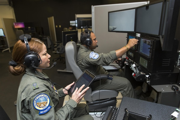 Maj. Maria Tejada-Quintana (left), a guest instructor at the Inter-American Air Forces Academy at Joint Base San Antonio-Lackland, oversees a student's flight simulation Oct 3, 2017. Tejada-Quintana is the only female flight guest instructor teaching international students from partner nations in the Western Hemisphere.