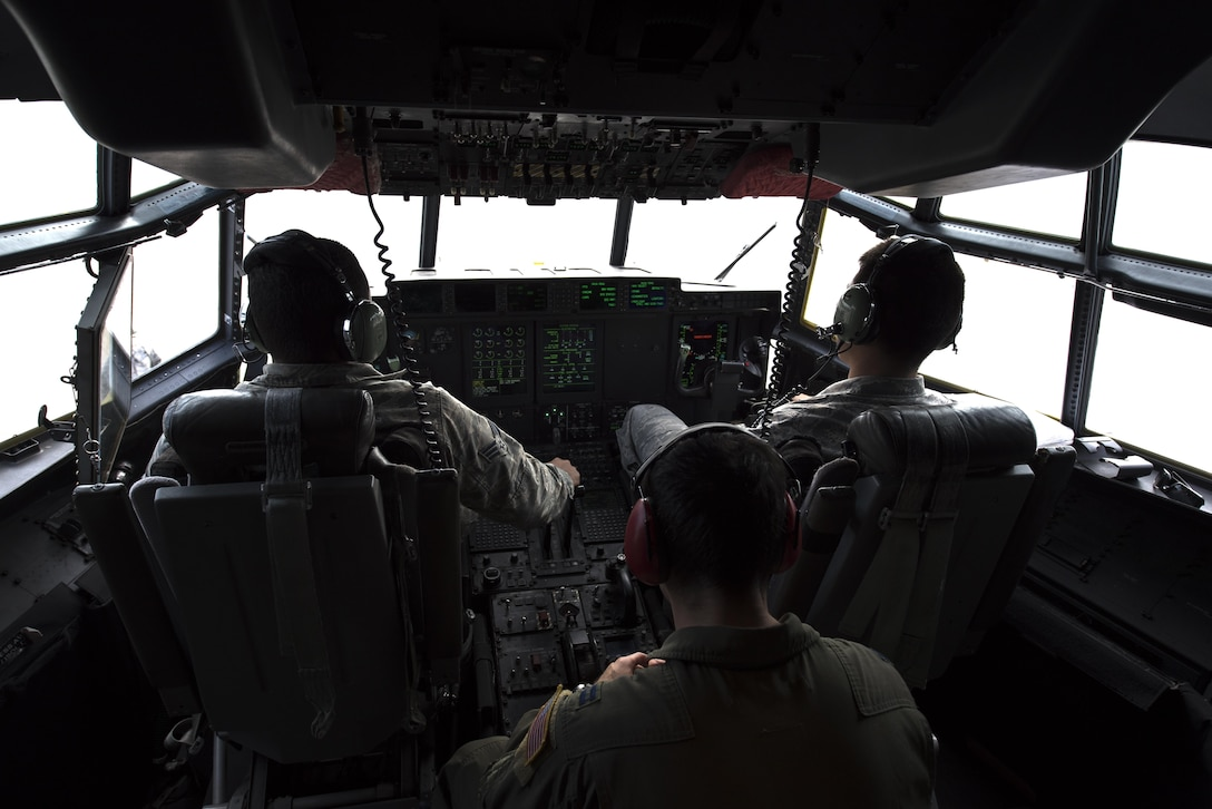 U.S. Airmen assigned to the 86th Aircraft Maintenance Squadron and 37th Airlift Squadron sit in the pilot seats of a C-130J Super Hercules during taxi to a parking spot on Ramstein Air Base, Germany, Oct. 13, 2017. Crew chiefs are responsible for preparing the aircraft for the next mission. (U.S. Air Force photo by Airman 1st Class Devin M. Rumbaugh)