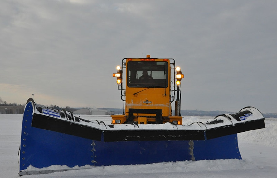A snow plow clears the runway at Wright-Patterson AFB. Severe weather events like a snow storm can wreak havoc on runways and streets on the installation, causing reporting delays or base closures. (U.S. Air Force photo)