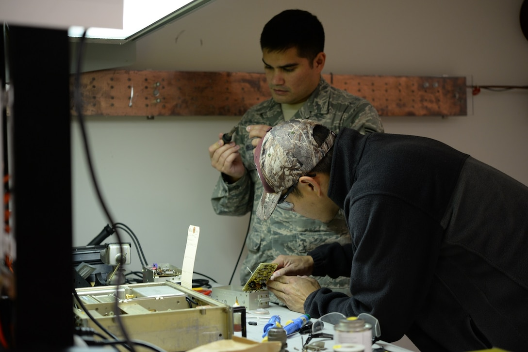 Senior Airman Jacob Hoeltje and Mark Kenner, 14th Operations Support Squadron Radar, Airfield and Weather Systems Flight (RAWS) technicians, fix a communications piece Nov. 3, 2017, on Columbus Air Force Base, Mississippi. Staff Sgt. Andrew Snyder, 14th OSS RAWS Assistant Noncommissioned Officer in Charge, said the 1C8X1 Radar and 1C8X2 Airfield Systems career fields merger Nov. 1, 2017, means more qualified technicians are now able to be spread across the RAWS mission. (U.S Air Force photo by Airman 1st Class Keith Holcomb)