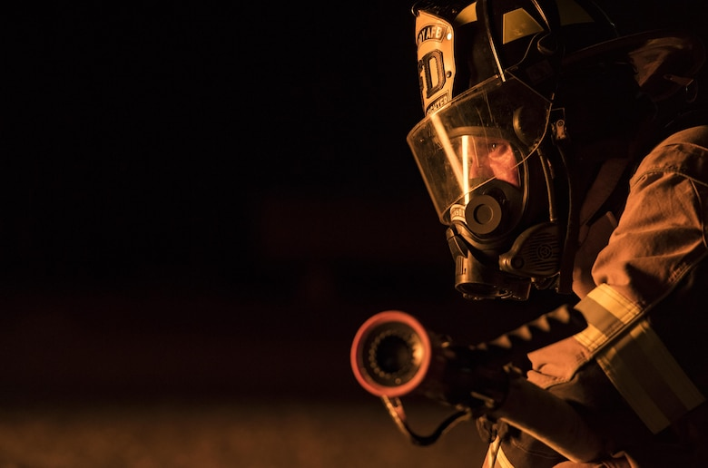A firefighter from the 23d Civil Engineer Squadron watches his colleagues put out a fire during nighttime live-fire training, Nov. 9, 2017, at Moody Air Force Base, Ga. Moody and the Valdosta Fire Department joined forces to prepare for the possibility of nighttime aircraft fire operations. (U.S. Air Force photo by Senior Airman Janiqua P. Robinson)