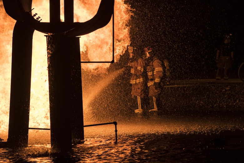 Firefighters from Moody Air Force Base, Ga. put out a blaze during nighttime live-fire training, Nov. 9, 2017, at Moody AFB, Ga. This training prepares participants for the possibility of nighttime aircraft fire operations. (U.S. Air Force photo by Senior Airman Janiqua P. Robinson)