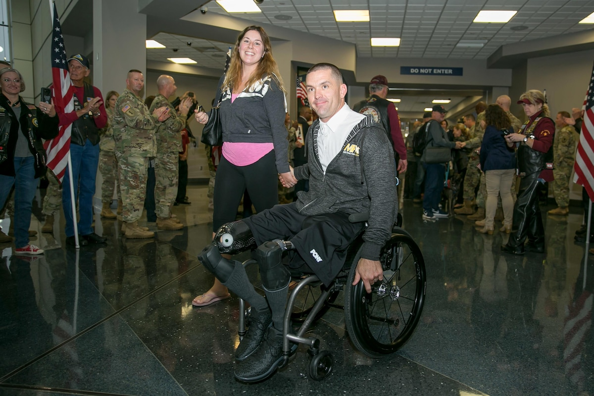 A wounded warrior in a wheelchair poses for a photograph.