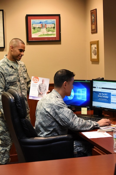 U.S. Air Force Staff Sgt. Eric Medina, 17th Force Support Squadron manpower analyst, and Col. Ricky Mills, 17th Training Wing commander, look at the Combined Federal Campaign website to sign up for this year's campaign at the Norma Brown building on Goodfellow Air Force Base, Texas, Nov. 8, 2017. The base's goal for the campaign this year is to raise 87 thousand dollars for charity. (U.S. Air Force photo by Airman 1st Class Seraiah Hines/Released)