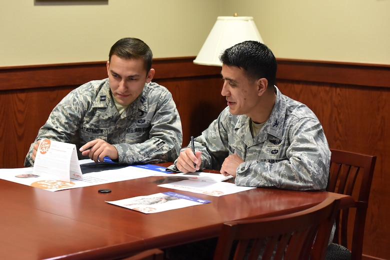 U.S. Air Force Col. Ricky Mills, 17th Training Wing commander, and Capt. Iskandar Atajanow 17th TRW chaplain, sign a Combined Federal Campaign paper pledge, donating to a charity of their choice, as an official start to this year's campaign at the Norma Brown building on Goodfellow Air Force Base, Texas, Nov. 8, 2017. This year, anyone wanting to sign up for the campaign may do so either with the pledge form or on the campaign's website. (U.S. Air Force photo by Airman 1st Class Seraiah Hines/Released)