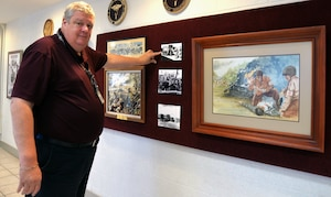 George Wunderlich, U.S. Army Medical Department Museum director, points to a section of historical photos and prints in the museum's revamped AMEDD Regimental Room, which is used for various activities from change of command and retirement ceremonies to receptions to training demonstrations. The renovations to the room are part of several improvements being made at the museum to enhance the visitor experience.