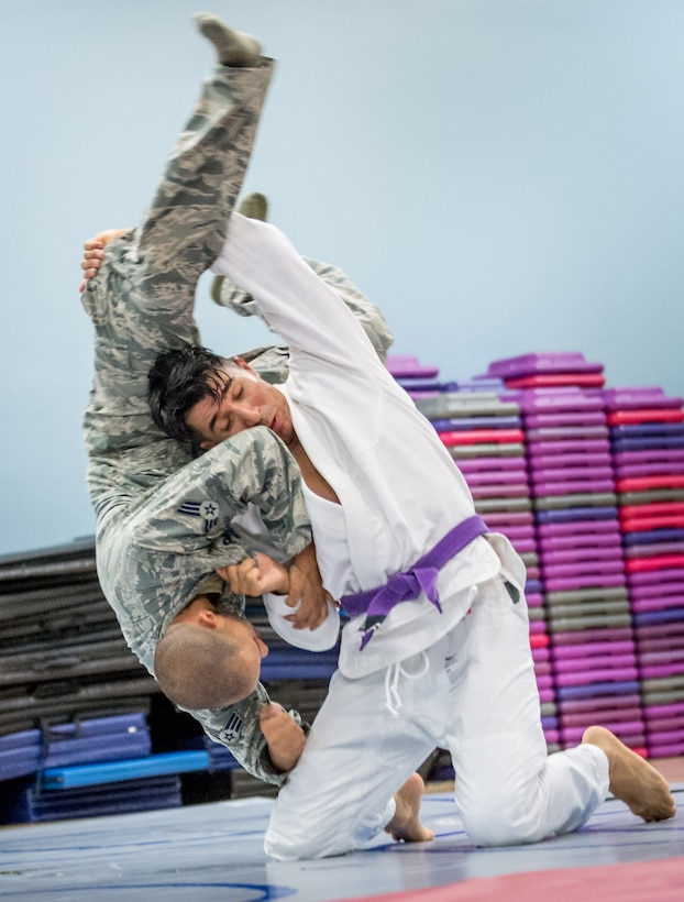 Tech Sgt. Jessie Sosa, 89th Maintenance Group special air missions crew chief, demonstrates a jiu-jitsu throw for Senior Airman Anthony Vallejos and other members of the 811th Security Forces Squadron at the Joint Base Andrews Tactical Fitness Center at JB Andrews, Md., Oct. 10, 2017. Sosa, a practitioner of Brazilian Jiu-Jitsu, often has joint and muscle strains after competitions and back pain from long flight hours which he treats with battlefield acupuncture allowing him to avoid the use of pain medications. (U.S. Air Force photo by J.M. Eddins Jr.)