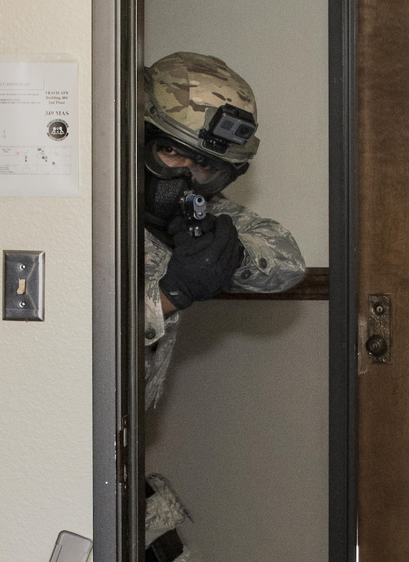 U.S. Air Force Airman 1st Class Christopher Boone, peers around a door frame during Defender Annual Refresher crucible training, Oct. 27, Travis Air Force Base, Calif.  60th SFS team members go through a 30-day period of intense training for the DART program. The teams of specially trained security forces personnel are dedicated to providing security for terrorist and criminal threat areas.