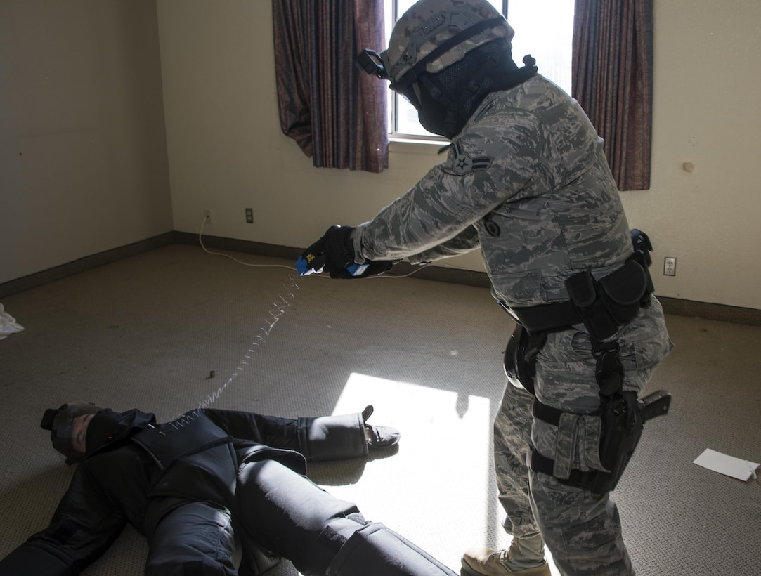 """U.S. Air Force Airman 1st Class Christopher Boone, 60th Security Forces Squadron, uses a non-lethal taser to take down an armed """"assailant"""" during Defender Annual Refresher crucible training, Oct. 27, Travis Air Force Base, Calif.  60th SFS team members go through a 30-day period of intense training for the DART program. The teams of specially trained security forces personnel are dedicated to providing security for terrorist and criminal threat areas."""