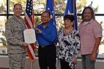 Lt. Gen. Lee K Levy II, Air Force Sustainment Center commander, presents Henry San Nicolas his 50-year service certificate, while his wife Dorothy and son Christopher join him during the presentation on Nov. 2, 2017, at Hill Air Force Base, Utah. (U.S. Air Force Photo by Alex R. Lloyd)