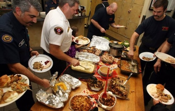 Several fire fighters gather around the table at their fire station to enjoy a home-cooked Thanksgiving Day meal.