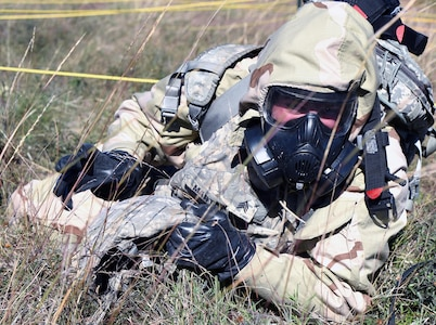 Sgt.Daniel Martin from the 1st Infantry Division low crawling though simulated wire during the chemical, biological, radiological and nuclear (CBRN) defense lane.