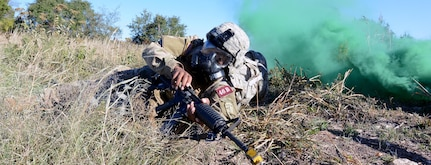 Avoiding simulated enemy fire and a chemical gas attack, Sgt. Rolando Fender from the Airborne and Ranger Training Brigade makes his way towards an injured Soldier while at the chemical, biological, radiological and nuclear (CBRN) defense lane. Photo by Jose E. Rodriguez, AMEDDC&S