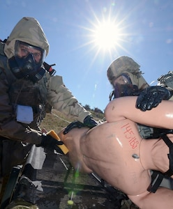 While wearing  Mission Oriented Protective Posture (MOPP) Level 4 gear, Sgt. Brett Reynolds and Sgt. Daniel Martin from the 1st Infantry Division treat a simulated chemical attack victim.