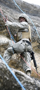 Staff Sgt.Lionel Semon, assigned to the Airborne and Ranger Training Brigade, climbing up the side of a cliff.