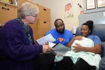 Helen Romeyn, a Family Advocacy nurse, gives informational booklets to Lei-Andrea Banks and her husband, Staff Sgt. Adrian Banks, the operations manager at the Bellamy Fitness Center, about newborns like their own, Kerrington, at Ellsworth Air Force Base, S.D., Nov. 8, 2017. The New Parent Support Program is a community-based program that serves families with children three years old and under. (U.S. Air Force photo by Airman 1st Class Thomas Karol)